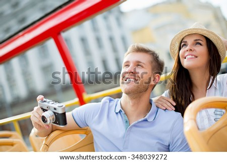 Young couple with a camera in a tour bus - stock photo