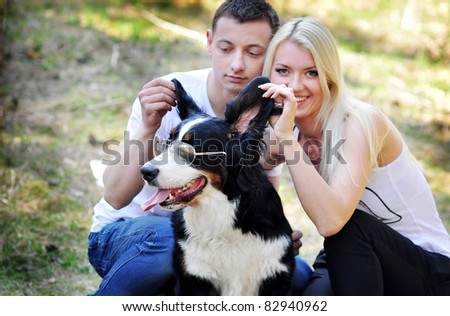 Young couple with a dog on the grass in the park - stock photo