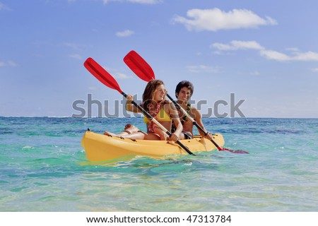 young couple with a kayak in hawaii - stock photo