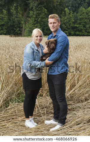 young couple with a labrador puppy outdoor