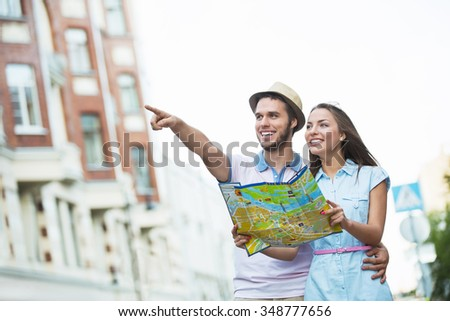 Young couple with a map on the street - stock photo