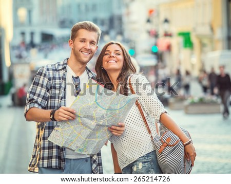 Young couple with a map outdoors - stock photo