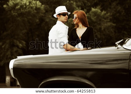 Young couple with a retro car against city park. - stock photo