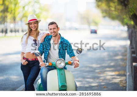 Young couple with a scooter outdoors - stock photo