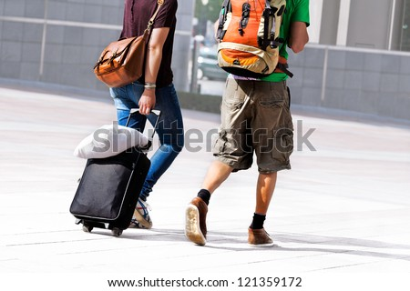 Young couple with a travel bag. Urban scene. - stock photo