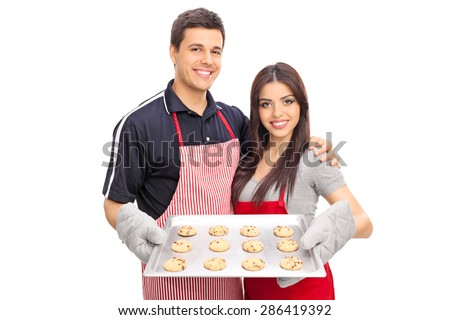 Young couple with aprons holding a baking pan full of chocolate chip cookies isolated on white background - stock photo