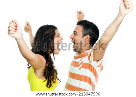 Young couple with arms raised shouting at each other.Isolated on white background. - stock photo