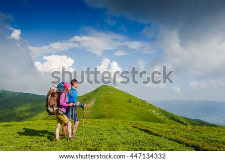 Young couple with backpack hiking in the mountains and enjoying valley view