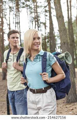 Young couple with backpacks trekking in forest - stock photo