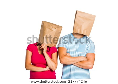 Young couple with bags over heads on white background - stock photo