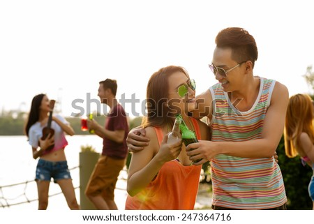 Young couple with beer bottles having fun at the sunset party - stock photo