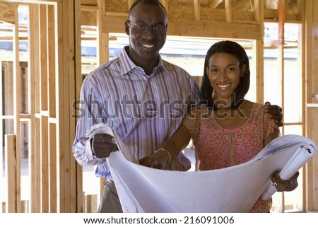 Young couple with blueprints in partially built house, smiling, portrait - stock photo