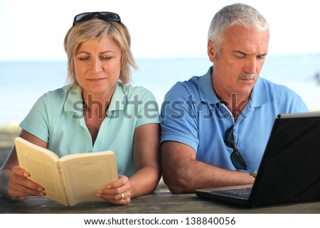 Young couple with book and computer - stock photo