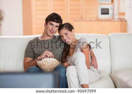 Young couple with bowl on popcorn watching a movie on the sofa - stock photo