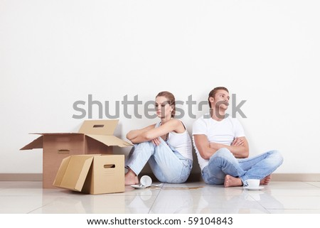 Young Couple with boxes and broken cup
