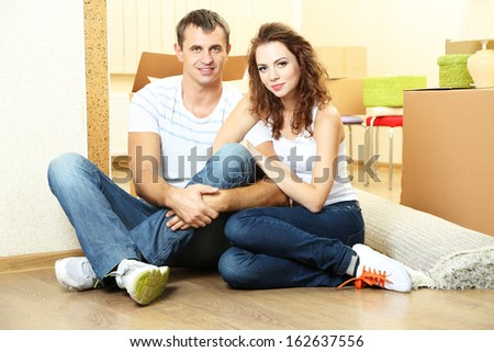 Young couple with boxes in new home on room background  - stock photo