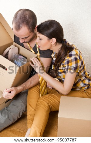 Young Couple with boxes in the new apartment sitting on floor and planning their future, dreaming about something positive - stock photo