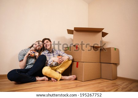 Young Couple with boxes of drinking coffee in the new apartment - stock photo