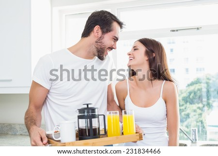 Young couple with breakfast on tray at home in the kitchen - stock photo