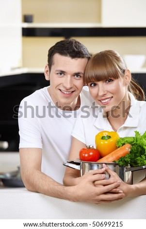 Young couple with capacity with vegetables in the foreground - stock photo