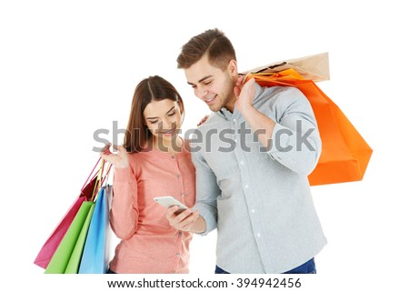 Young couple with colorful shopping bags isolated on white - stock photo
