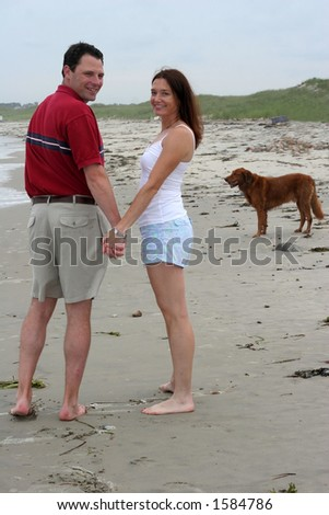 young couple with dog at beach - stock photo