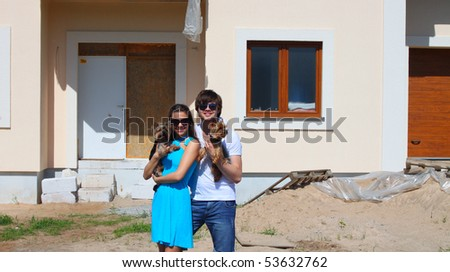 Young couple with dog in front of their new house - stock photo