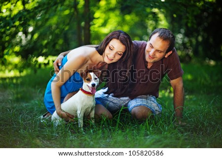 Young couple with dog on picnic in park - stock photo