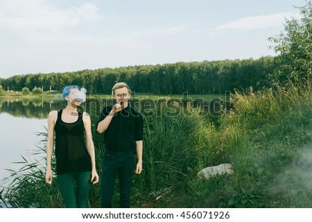 young couple with dyed hair smoking electronic cigarettes on the lake