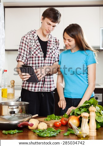 Young couple  with eBook in home kitchen