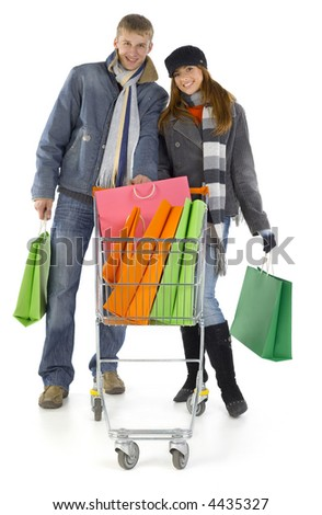 Young couple with full trolley. Smiling and looking at camera. Isolated on white in studio. Whole body, front view - stock photo