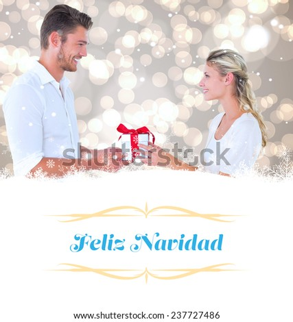 young couple with gift against Christmas greeting card - stock photo