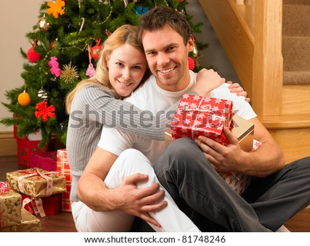 Young couple with gifts in front of Christmas tree - stock photo