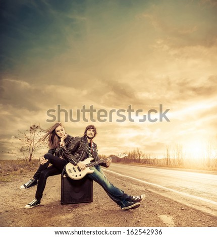 young couple with guitar on a fall freeway to horizon - stock photo