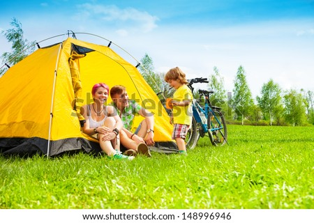 Young couple with kid sitting in the tent on a bike hiking trip - stock photo
