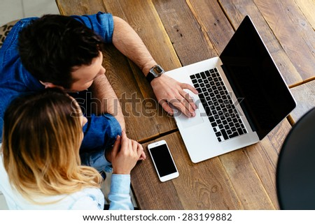 young couple with laptop at cafe against wooden table - mockup - stock photo