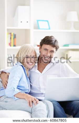Young couple with laptop on a couch - stock photo