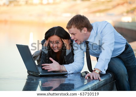 Young couple with laptop on the embankment of river. - stock photo