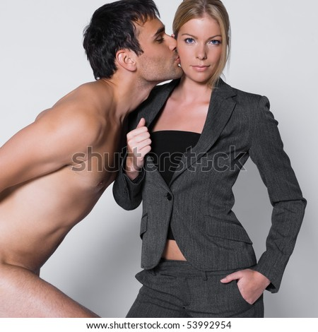 young couple with man naked in studio on isolated grey background with man kissing the woman on the cheek