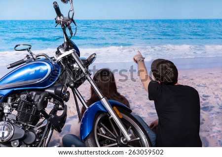 Young Couple with Motorbike Sitting on White Sand at the Beach While Looking at the Tranquil Ocean on a Tropical Climate. - stock photo