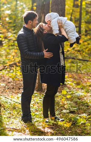 Young couple with newborn baby outdoors in autumn