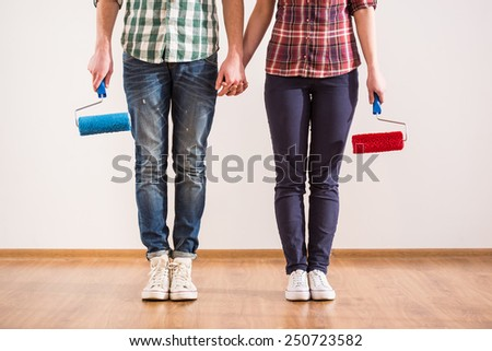 Young couple with paint roller, while doing repair at home. - stock photo