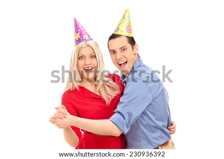 Young couple with party hats dancing isolated on white background - stock photo