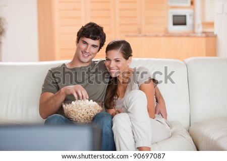 Young couple with popcorn on the sofa watching a movie - stock photo