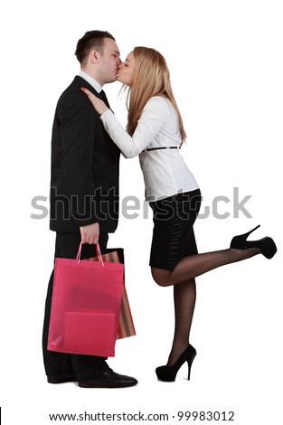 Young couple with shopping bags kissing against a white background.