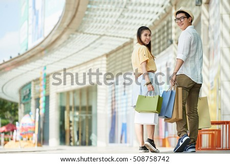 Young couple with shopping bags looking at camera