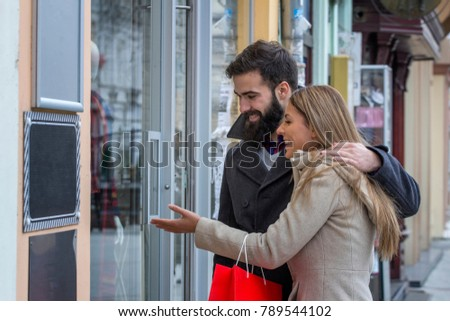 Young couple with shopping bags looking at the shop and he is hug her with one hand and she is showing with hand on window