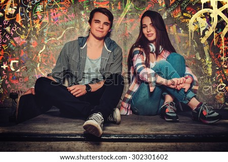 Young couple with skateboard outdoors against graffiti painted wall - stock photo