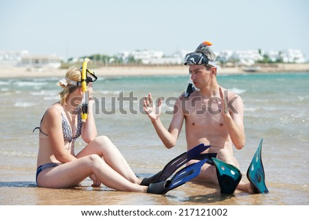 Young couple with snorkel gear sharing impressions on red sea beach at vacations - stock photo