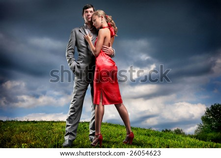 Young couple with storm cloudy sky - stock photo